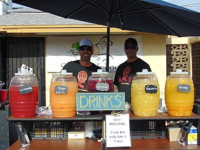 two men behind a drink stand